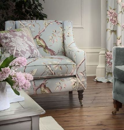 Prestigious Textiles -  Country House Fabric Collection - Curtains and padded armchair with bird and flower print, lilac, cream and green stripe and lace effect cushions, wooden table and white vase