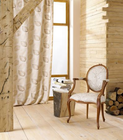 Prestigious Textiles -  Countryside Fabric Collection - A gold grand curtain with detailed stitched leaf decoration, and an antique chair with gold classic upholstery