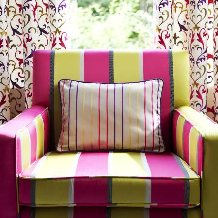 Prestigious Textiles -  Couture Fabric Collection - A vivid pink and green modern upholstered armchair with a pink and yellow striped pillow, and white curtains with colourful classic swirls