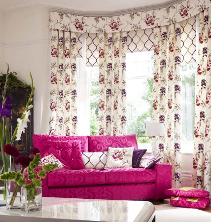 Prestigious Textiles -  Couture Fabric Collection - A vivd pink upholstered couch with a swirly pattern, white cushions with flower and swirl decorartion, and white curtain pelmet with flowers