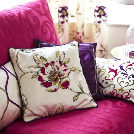Prestigious Textiles -  Couture Fabric Collection - White cushion with purple lining and a detailed red floral print, with variously decorated modern cushions on a vivd pink pholstered couch