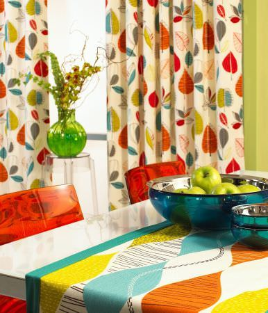 Prestigious Textiles -  Delamere Fabric Collection - Modern tablecloth in lively colours and a bead-type decoration, and white curtains with a modern leaf pattern in autumn colours