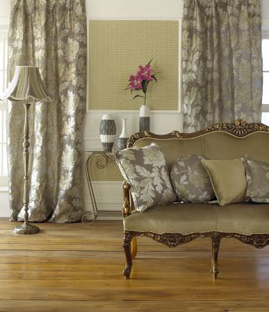 Prestigious Textiles -  Delano Fabric Collection - Antique couch with gold fabric upholstery with silver cushions, and silver curtains with large classic floral decoration