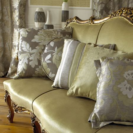 Prestigious Textiles -  Delano Fabric Collection - Classic gold fabric cushions with flower, stsripe and leaf decorations on an antique gold upholstered chair