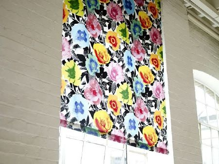 Prestigious Textiles -  Diva Fabric Collection - White window blind patterned with black and grey leaves and large, bright flowers in shades of pink, blue, green, yellow and orange-red
