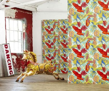 Prestigious Textiles -  Diva Fabric Collection - Parrot print wall coverings with pineapples in orange, red, cobalt blue and lime green, with a merry-go-round horse and a red and white sign