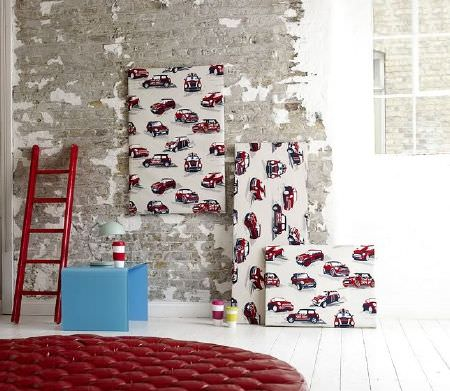 Prestigious Textiles -  Diva Fabric Collection - Short red ladder beside a light blue square side table, with a lamp, striped cups and wall hangings covered in an off-white and red Mini print