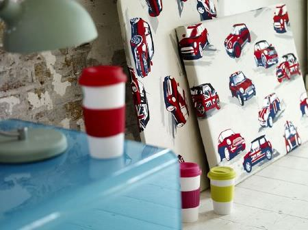 Prestigious Textiles -  Diva Fabric Collection - Red and blue Mini Coopers printed on off-white wall hangings, beside a cobalt blue plastic side table and multicoloured striped coffee cups