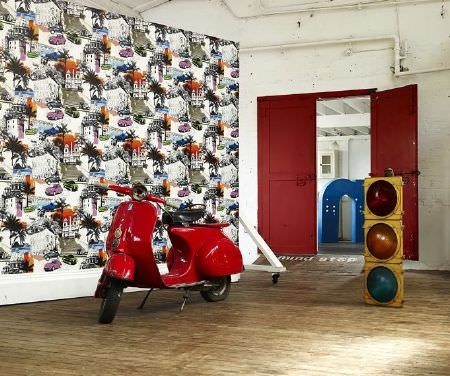Prestigious Textiles -  Diva Fabric Collection - Bright red Vespa beside a set of traffic lights and a panel covered in a repeated city scene in white, green, black, purple, blue and orange