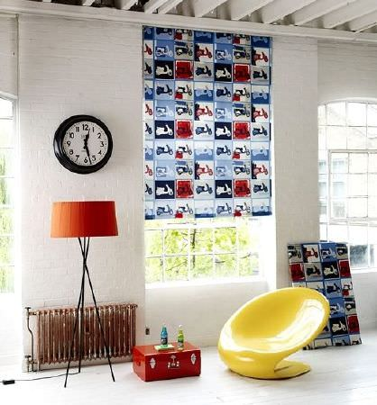 Prestigious Textiles -  Diva Fabric Collection - Red, white, blue and grey Vespa print blind and wall hanging with a low round yellow plastic chair, orange shaded floor lamp and black clock