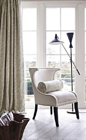 Prestigious Textiles -  Dorchester Fabric Collection - A modern padded white armchair with dark legs and a white bolster cushion, a black anglepoise floor lamp and oyster curtains