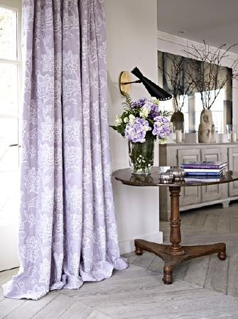 Prestigious Textiles -  Dorchester Fabric Collection - Lilac and white floral curtains, a round wood table with a large glass vase, a black wall light, a grey cabinet and a mirror