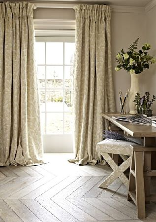 Prestigious Textiles -  Dorchester Fabric Collection - Pale beige and white patterned fabric on curtains and a folding stool, with a wooden table and stepladder, and a cream vase
