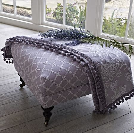 Prestigious Textiles -  Dorchester Fabric Collection - A large grey padded footstool with embroidered white checks, with a matching floral, pompom trimmed throw, and lavender