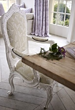 Prestigious Textiles -  Dorchester Fabric Collection - An ornately carved white wood armchair with apale green and white leaf print back and seat, with a wood table, and curtains