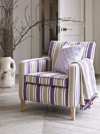 Prestigious Textiles -  Dorchester Fabric Collection - A purple, light grey and white striped armchair, draped with a matching throw with a pompom trim, and an embroidered cushion