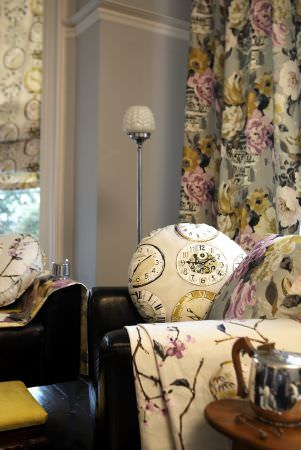 Prestigious Textiles -  Drawing Room Fabric Collection - Modern meets formal sitting room - Roman blinds, curtains, throws and cushions - clock and floral designs