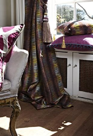 Prestigious Textiles -  Eclipse Fabric Collection - Luxurious fabrics in dark purple, grey, blue and green on patterned curtains and two cushions, by a white and gold armchair