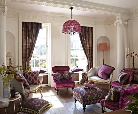 Prestigious Textiles -  Eclipse Fabric Collection - Luxurious purple patterned fabrics covering armchairs, a footstool, curtains and cushions, with 2 white and gold armchairs