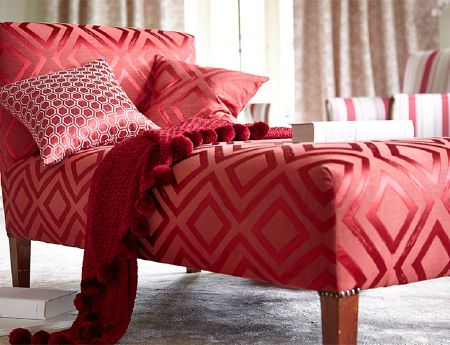 Prestigious Textiles -  Eden Fabric Collection - Bright shades of red making up a bold geometric patterned chaise longue, a plain tasselled throw and two scatter cushions