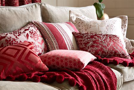 Prestigious Textiles -  Eden Fabric Collection - A sumptuous red throw with red and white patterned and striped scatter cushions on a light grey-white coloured fabric sofa