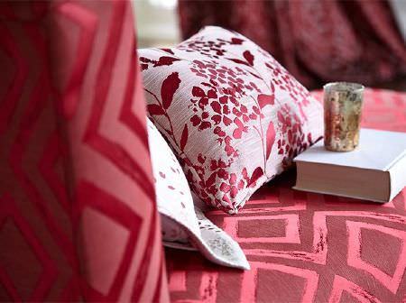 Prestigious Textiles -  Eden Fabric Collection - A bold geometric and a stylised floral print on a sofa and cushion, with metallic foil printing in bright red and grey-white