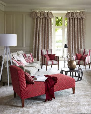Prestigious Textiles -  Eden Fabric Collection - Patterned curtains, a white lamp, a silver rug, a red chaise longue, striped armchairs, a grey sofa, cushions and a table
