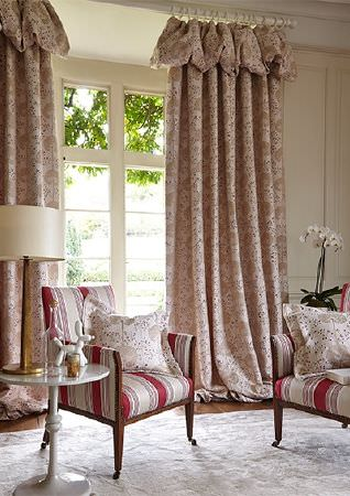 Prestigious Textiles -  Eden Fabric Collection - Long white curtains featuring a subtle pattern, with red and white striped armchairs, patterned cushions, a table and a lamp