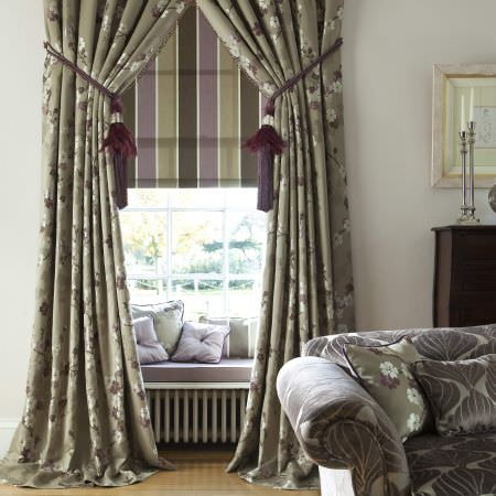 Prestigious Textiles -  Elysee Fabric Collection - Green-grey curtains with a simple floral design, green and purple roman blinds, and a purple seating pad with colourful cushions