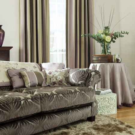 Prestigious Textiles -  Elysee Fabric Collection - A brown-grey upholstered couch, with a white floral blanket with purple lining, and purple cushions with stripes, a green curtain