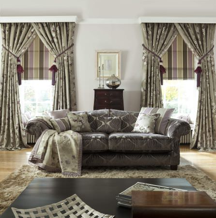 Prestigious Textiles -  Elysee Fabric Collection - A classic couch with light grey upholstery, and green blanket and striped cushions, in front of olive green curtain pelmets with flowers