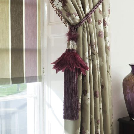 Prestigious Textiles -  Elysee Fabric Collection - A deep purple tie back curtain rope with feathers and tassels, with a green curtain with white flowers and a striped roman blind