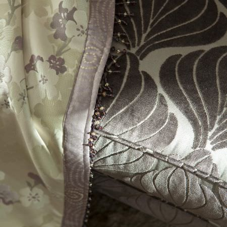 Prestigious Textiles -  Elysee Fabric Collection - Light green blanket with flowers and purple lining on a grey upholstery with a simple leaf pattern from the Elysee fabric collection
