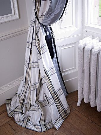 Prestigious Textiles -  Empire Fabric Collection - Simple checks in shades of grey on long white curtains edged in plain blue-grey fabric, with adark blue tassel tieback