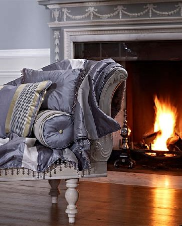 Prestigious Textiles -  Empire Fabric Collection - A lit fire behind a white wood chaise longue loaded with satin effect throws and cushions in plain and striped blue-grey