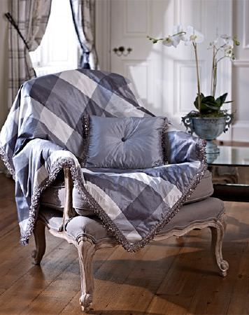 Prestigious Textiles -  Empire Fabric Collection - A plain cushion and a checked throw in white and blue-grey with a satin effect finish, draped over agrey and white armchair