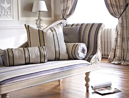 Prestigious Textiles -  Empire Fabric Collection - A white wood chaise longue with striped seat, bolster and scatter cushions in white, purple and pale gold colours