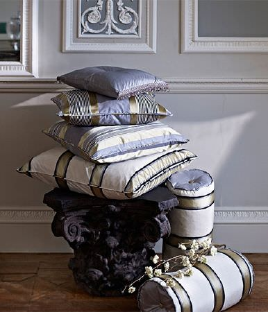 Prestigious Textiles -  Empire Fabric Collection - A carved black stool with satin effect scatter and bolster cushions with striped patterns in white, light gold and grey-blue