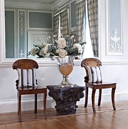 Prestigious Textiles -  Empire Fabric Collection - A large mirrored urn on a carved black wooden stool, between two stylish wooden chairs withtwo striped scatter cushions