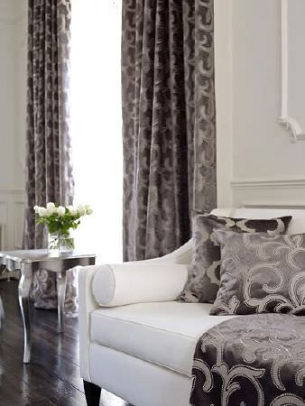 Prestigious Textiles -  Emporium Fabric Collection - Curtains, cushions and fabric with a matt grey swirl print on a metallic grey backdrop, with a white sofa and a silver side table