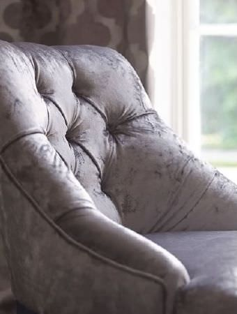 Prestigious Textiles -  Emporium Fabric Collection - Grey velour armchair in front of brown and cream patterned curtains