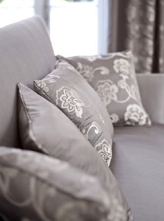 Prestigious Textiles -  Emporium Fabric Collection - Grey sofa with  matching double-sided grey scatter cushion, and three other grey cushions with a stylish floral design