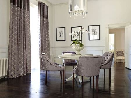 Prestigious Textiles -  Emporium Fabric Collection - Four grey velour armchair-cum-dining chairs around a large, round, cream wood table, with a cream vase and grey patterned curtains