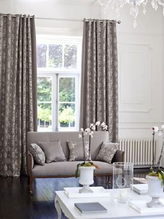 Prestigious Textiles -  Emporium Fabric Collection - Small sofa in plain grey fabric, with grey and silver cushions and curtains, a white coffee table and glass and opaque white vases