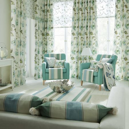 Prestigious Textiles -  English Rose Fabric Collection - An azure blue easy chair with white and blue striped and floral cushions, a white and blue tablecloth, and white curtains with blue flowers