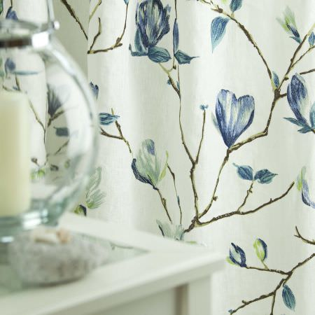 Prestigious Textiles -  English Rose Fabric Collection - A close-up of a white curtain with blue leaf and flower pattern from the English Rose fabric collection