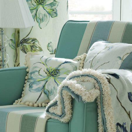 Prestigious Textiles -  English Rose Fabric Collection - An azure blue upholstered easy chair with two flower decorated cushions and a light blue blanket with a flower print
