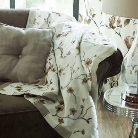 Prestigious Textiles -  English Rose Fabric Collection - A white blanket with flower prints and a light brown striped lining on a grey upholstered couch, and a white curtain with brown leaves