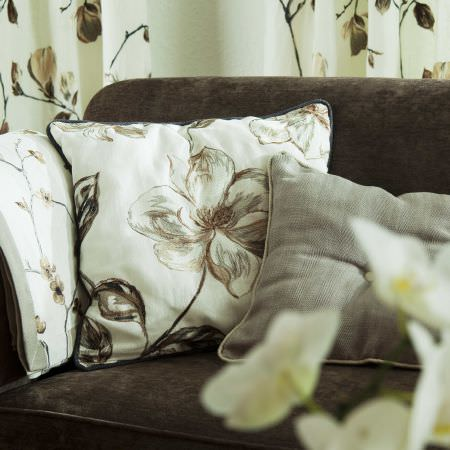 Prestigious Textiles -  English Rose Fabric Collection - A white cushion with brown and silver flower impressions, a plain grey cushion with herringbone, on a black upholstered couch