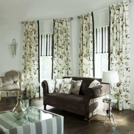 Prestigious Textiles -  English Rose Fabric Collection - White curtains with autumn brown leaves and striped roman blinds encircling a classic modern living room with a black upholstered couch